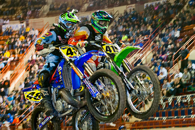 Two bikes and riders locked together in a jump. Photos Motorama 2013