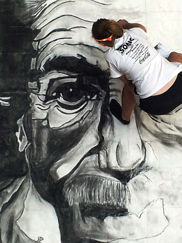 A talented young artist works one her charcoal portrait of Albert Einstein at Chalk It Up!