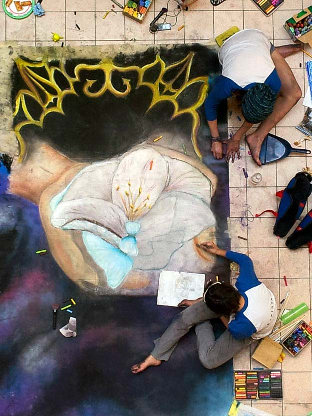 Two artist work on the mural at Chalk It Up!