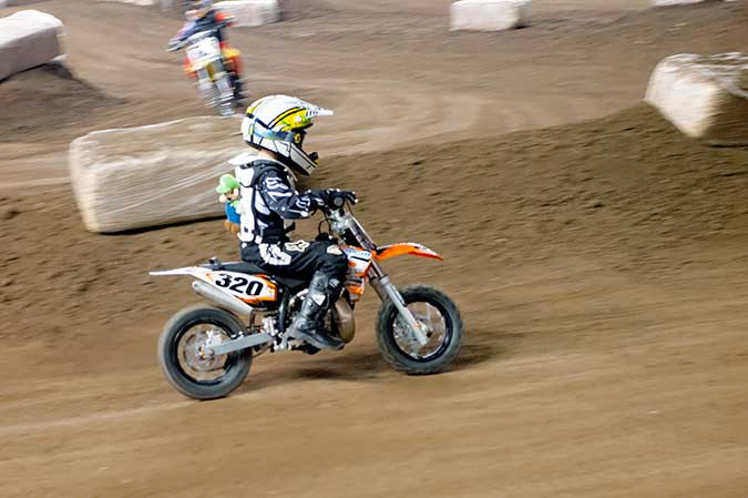 Luigi riding along on the back of a child racer at arenacross Motorama 2014