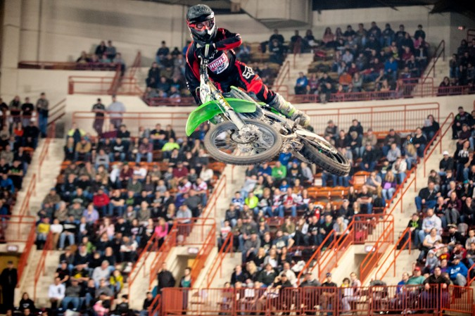 A dirt bike sores overhead in the main arena of the Pennsylvania Farm Show Complex at Motorama 2015