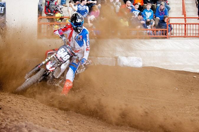 A dirt bike kicks up a cloud of dirt and dust in the main arena at Motorama 2015 in Harrisburg, Pennsylvania.