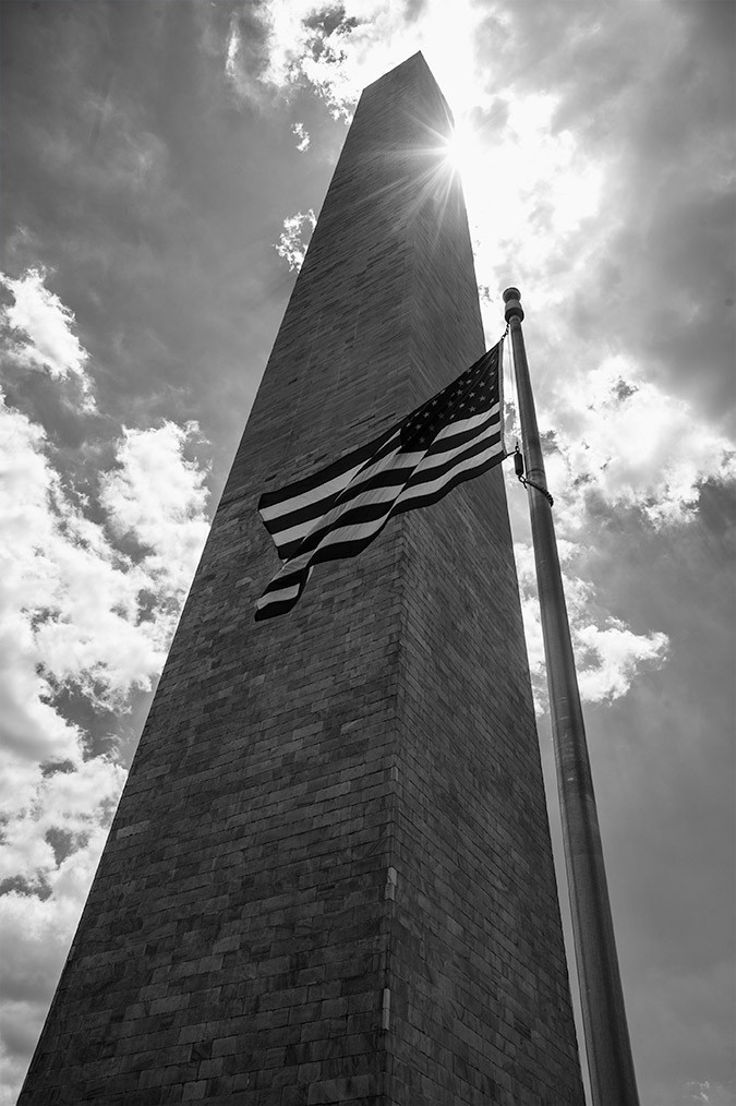 A photo of the US flag flying below the Washington Monument on the National Mall in Washington, DC.