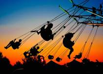 Kids on carnival swings at sunset