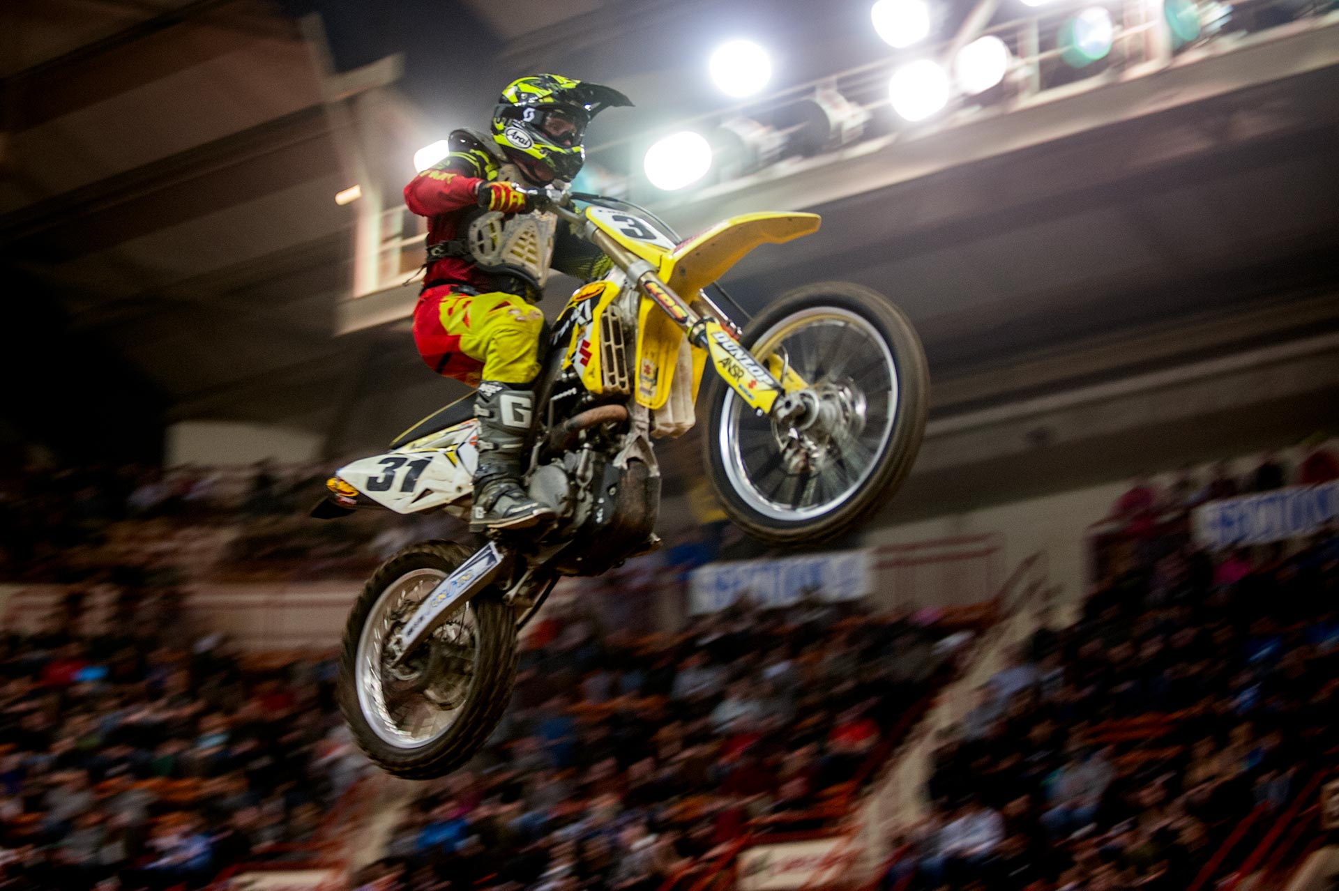 A bike flying through the air at the arenacross races.